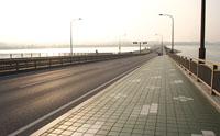広くとられた歩道で海風に吹かれながら夕陽のオレンジと海の青のコントラストを楽しむ。