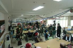 小谷園にて、今年最後となる行事として、「クリスマス☆忘年会」が12月22日(金)開催されました。当日は、ケンタッキーチキン・握り寿司・さしみ・ドーナツ等の普段召し上がることのない料理がご用意され、利用者様に大変喜ばれ、「チキンやマーサッサー」とおかわりを頼む方が多く見受けられました。 また、サンタさんにふんした職員が姿を現し、プレゼントを配ると「だーわんにんかい」と満面の笑み浮かべていました♪ ある男性利用者様は、ノンアルコールビールを嬉しそうに飲んでる姿が、こちらまで嬉しく感じました。 今年も大成功の「クリスマス☆忘年会」でした♪
