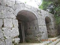 <b>崇元寺石門</b> 第一門及び石牆は、正面中央の切石積み三連の棋門(アーチ門)とその左右に延びる両掖門を備えた琉球石灰岩のあいかた積みの石壇であり、沖縄の石造拱門の代表的なものである。