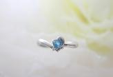 ハートの形のブルートパーズが輝くリング。   プラチナのリボンと小さなダイヤがハートを柔らかくみせてくれます。